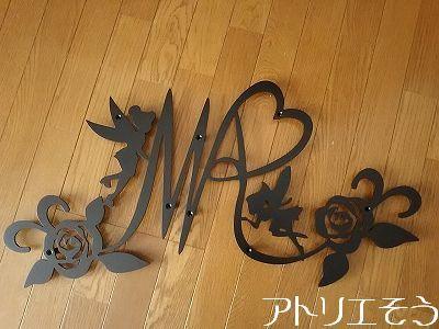 アトリエそうデザイン制作のロートアイアン風アルミ製妻飾りです。イニシャルMとAとRに薔薇と妖精のモチーフを組み合わせた素敵な妻飾りの写真です。