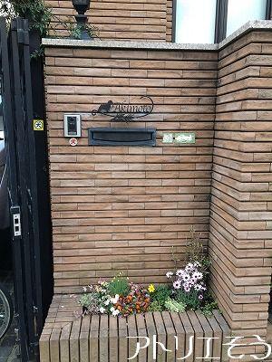 アルミ製妻飾り専門店アトリエそうデザイン制作の犬と小麦モチーフのステンレス製表札の設置写真