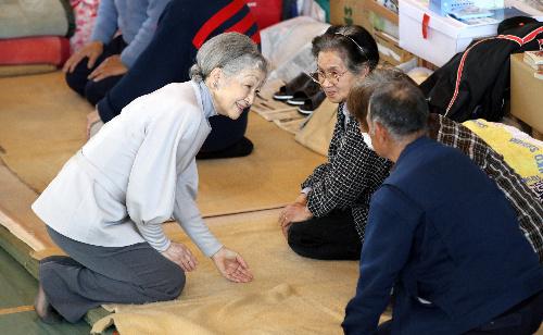 避難所を訪れ、被災した人たちと話す皇后さま=2011年4月27日、宮城県南三陸町の歌津中学校(スリッパなし)