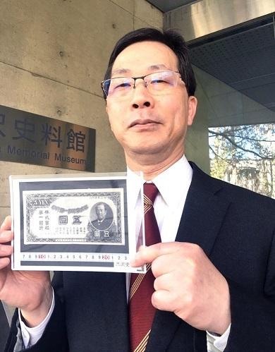 渋沢栄一の肖像画が入った5円紙幣を手にする渋沢史料館館長