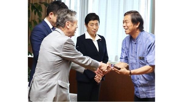 共産党の穀田恵二氏と笑顔で握手する謝花副知事(右)。立憲民主党の辻元国対委員長(中央)らが同席した=10日、県庁
