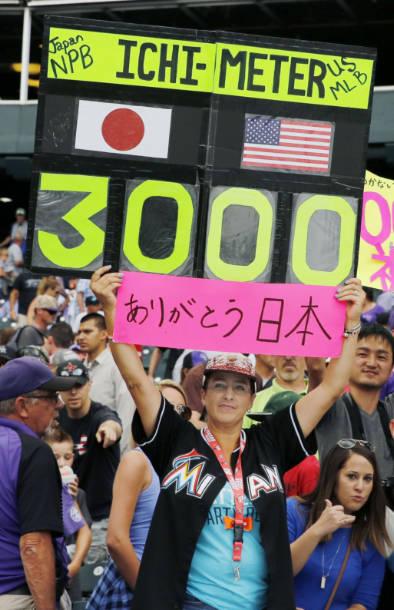 マーリンズのイチロー外野手が米大リーグ通算3千安打を達成し、数字が入った「イチ・メーター」と「ありがとう日本」と書かれたボードを掲げるエイミー・フランツさん=7日、デンバー(共同)