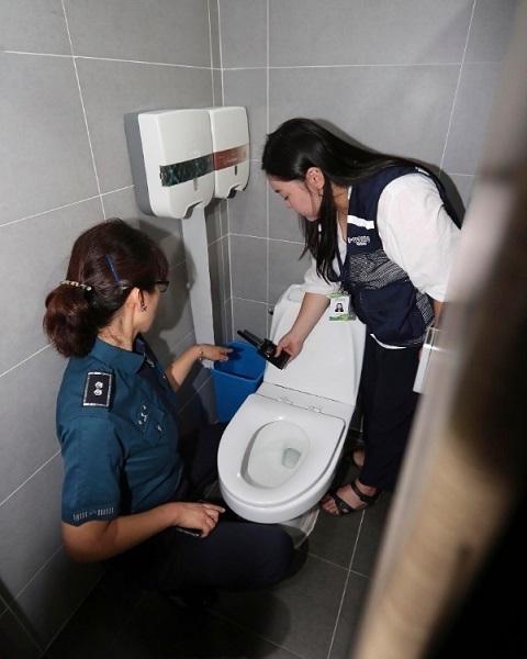 隠しカメラがないか女性用トイレを捜索する韓国の女性警察官(EPA=時事)