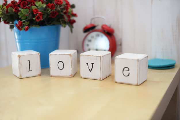 letters-wooden-word-cubes-love-table-with-red-alarm-clock-with-bouquet-flowers_73106-166.jpg
