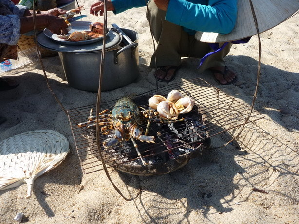ビーチで炭火を使って海老や貝を焼くおばちゃん_サイズ変更