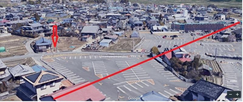 飯田市のリニア駅予定地。赤い線が中心線。赤い矢印が、Kさん夫妻を撮影した場所。畑は用地買収の対象になりそうだ。