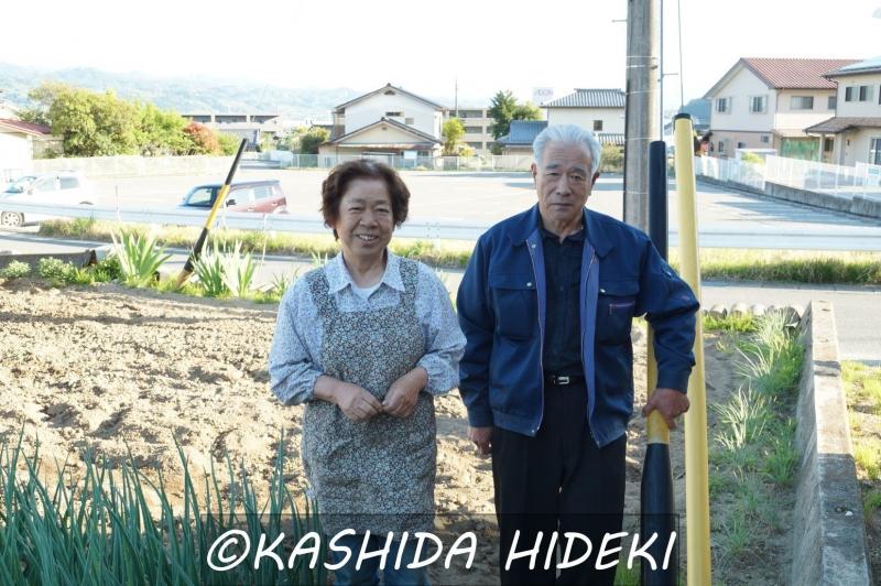 自身の畑の前に立つKさん夫妻。後ろに見えるのが、リニア駅予定地である駐車場。