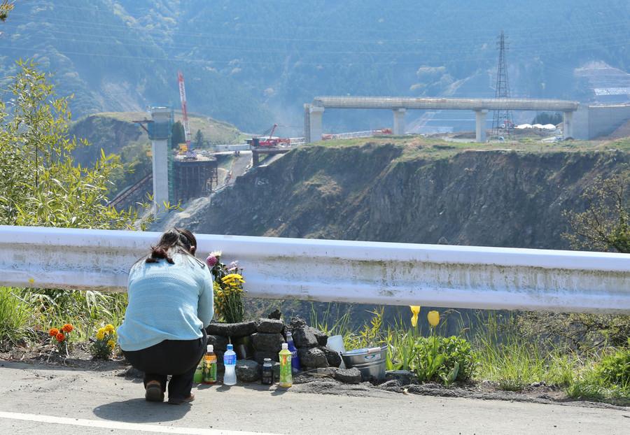 阿蘇大橋付近で土砂崩れに巻き込まれて犠牲となった大学生の冥福を祈る女性。奥は新たに建設中の阿蘇大橋=13日午後、熊本県南阿蘇村